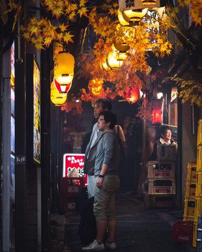 Man standing by illuminated lantern at night