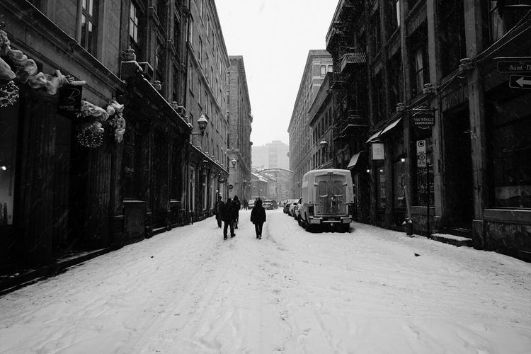 Man standing on snow covered street in city