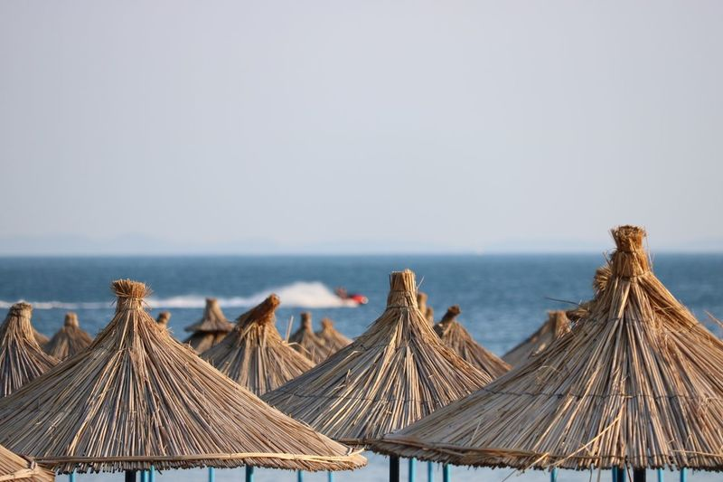 Thatched roofs at beach against clear sky
