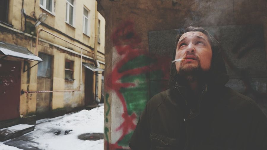 Man looking up while smoking cigarette against graffiti wall during winter in city