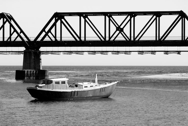 Fisherman boat on the water by the railroad bridge with calm water and blue sky Transportation Water Nautical Vessel Mode Of Transportation Sea Bridge Bridge - Man Made Structure Nature Sky Waterfront Connection Built Structure Day Travel No People Architecture Outdoors Travel Destinations Fishing Boat Blackandwhite Black And White Black And White Photography Railroad Track Railroad Bridge Railroad Bridge In Background