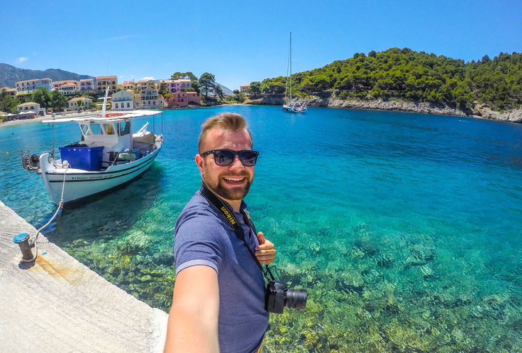 Water Sunglasses Portrait Real People One Person Smiling Leisure Activity Looking At Camera Lifestyles Glasses Nature Blue Sea Fashion Day Sunlight Happiness Sky Casual Clothing Outdoors Turquoise Colored Selfie Mountain Greece Kefalonia
