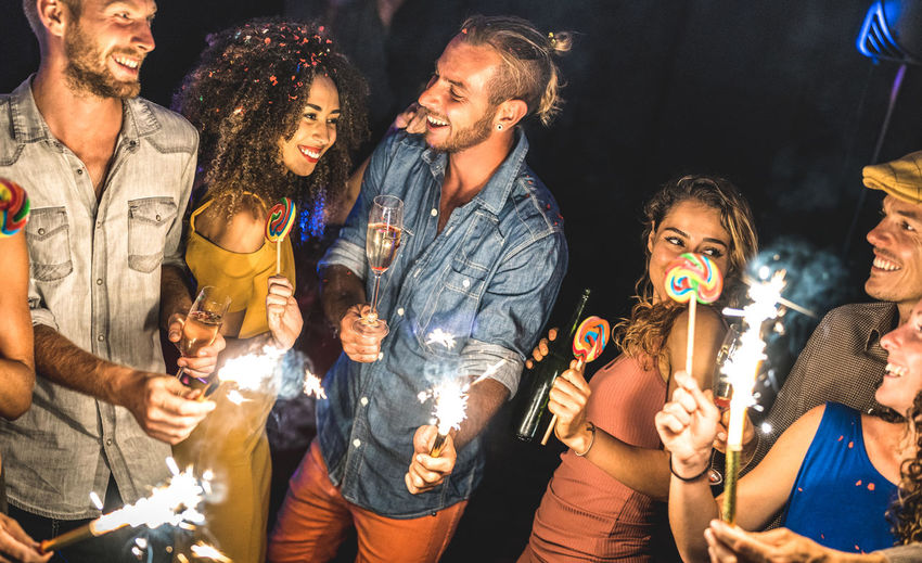 Cheerful of friends partying outdoors at night