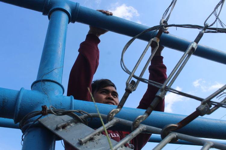 Low angle view of boy on slide at playground