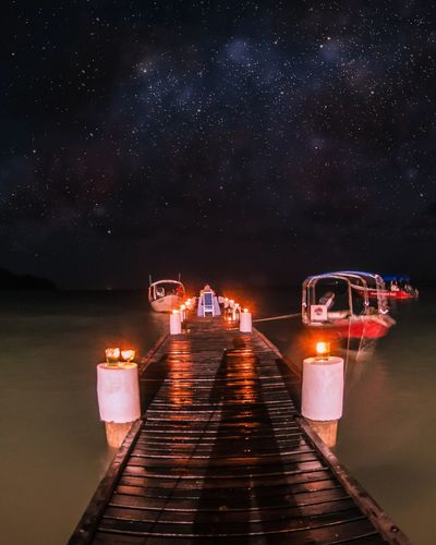Illuminated pier amidst lake against sky at night