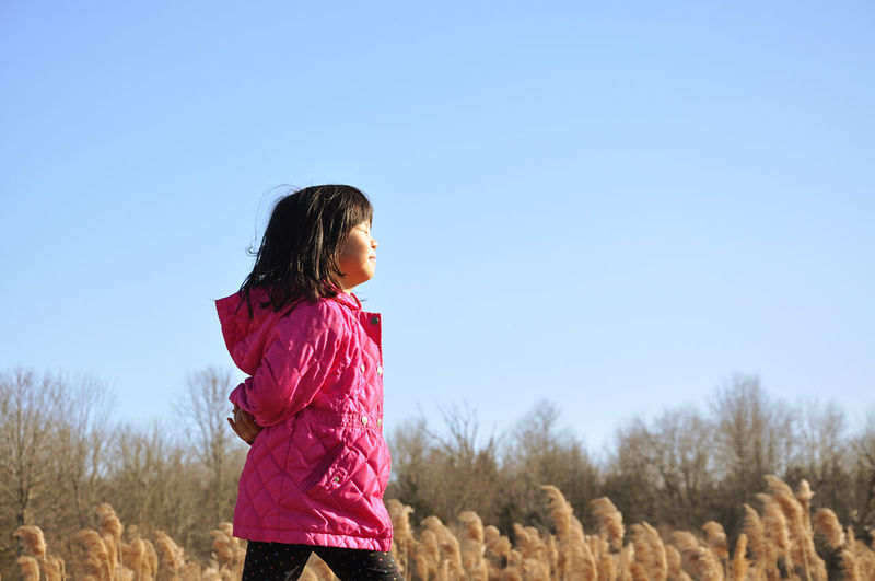 Girl standing on field against clear sky