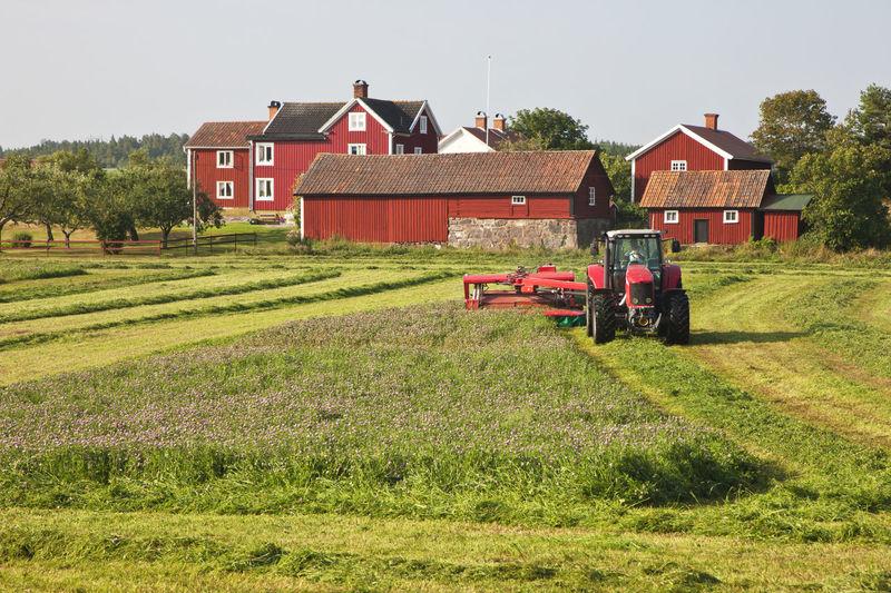 Tractor on field by houses against clear sky