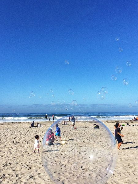 In the bubble EyeEm Team EyeEm Gallery EyeEm Best Shots Bubbles Bubble Soap Bubble Beach Land Sea Water Sand Sky Real People Blue Horizon Over Water People Outdoors Leisure Activity Clear Sky
