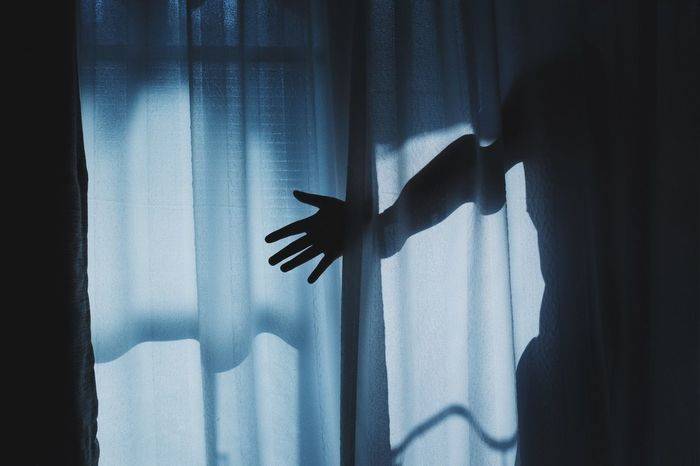 SHADOW OF PERSON HAND ON CURTAIN AT HOME