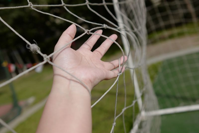 Close-up of hand holding goal post net