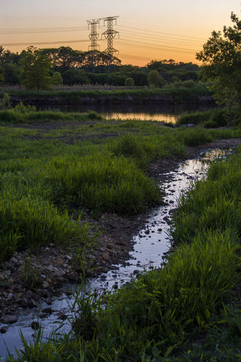 Scenic view of stream in field against sky at sunset
