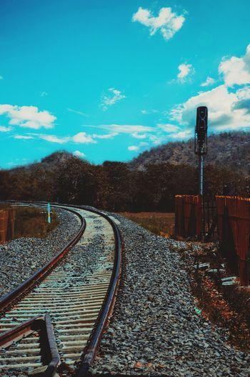 Railroad tracks amidst trees against blue sky