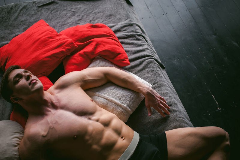 High angle view of shirtless muscular male model lying on bed at home