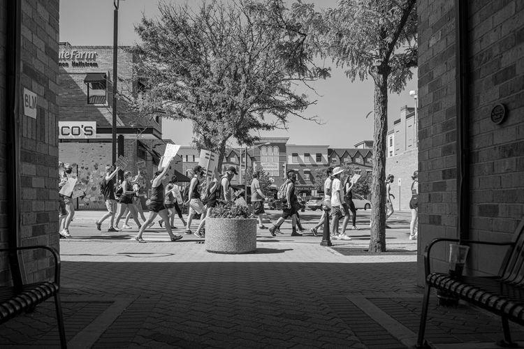 People on sidewalk by building in city