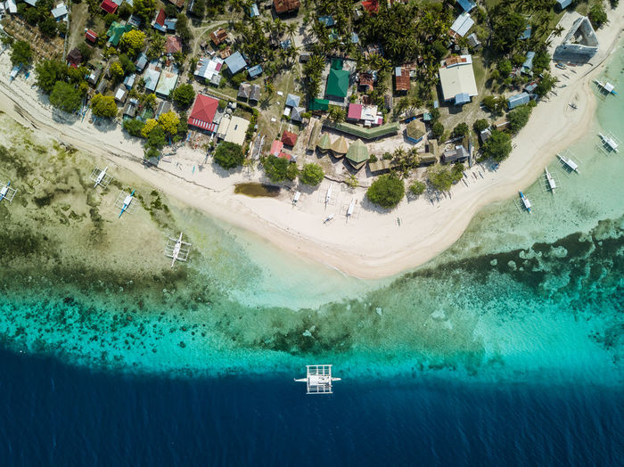 Bird's eye drone picture of a boat in the clear waters of pamilacan island, bohol, philippines