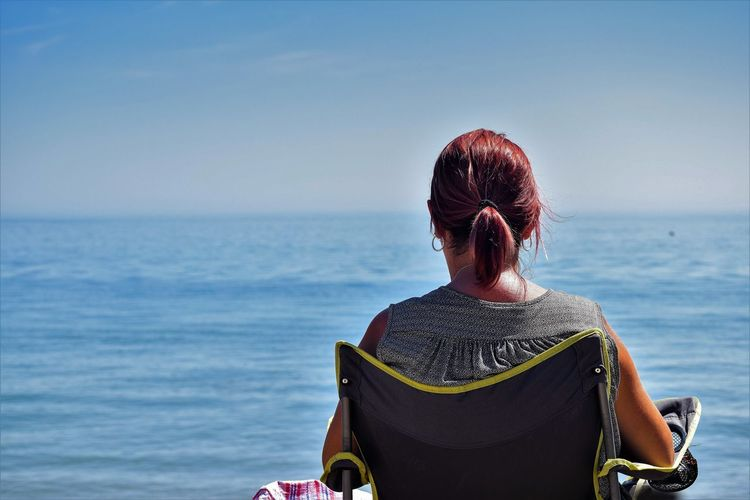 Rear View Of Mature Woman Relaxing On Chair At Beach Against Sky During Sunny Day