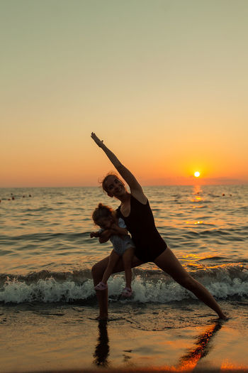 Sea Sunset Beach Sky Water Land Real People Lifestyles Leisure Activity Orange Color Horizon Over Water Full Length Horizon Scenics - Nature Beauty In Nature Women Human Arm One Person Motion Arms Raised Yoga Yoga Pose Daughter Warrior Pose Family Sport