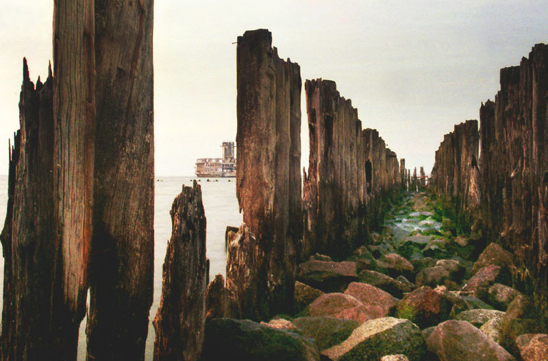 Weathered wooden posts by rocks at beach against sky