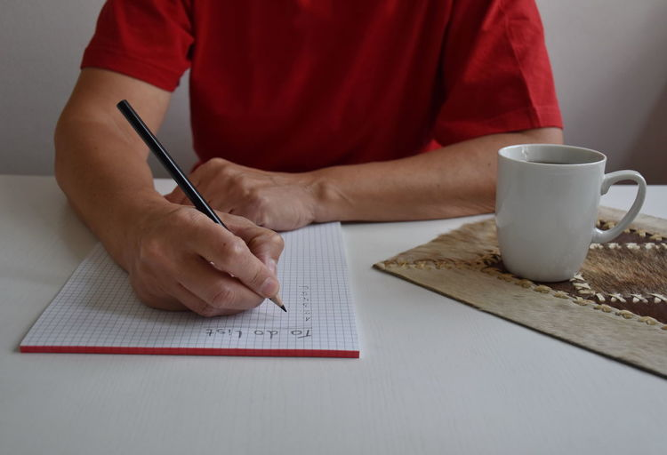 Writing Pen Midsection Table Human Hand One Person Indoors  Hand Cup Mug Paper Lifestyles Real People Holding Text Coffee Cup Sitting Human Body Part To Do List White Red
