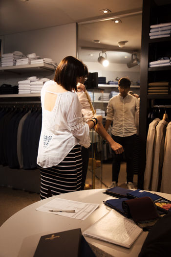 Business Suit Tailor Work Adult Business Casual Clothing Fancy Illuminated Indoors  Lifestyles Men Model Occupation People Real People Retail  Shopping Standing Store Tailormade Three Quarter Length Two People Women Young Adult