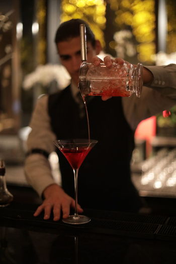 Bartender pouring drink at bar counter