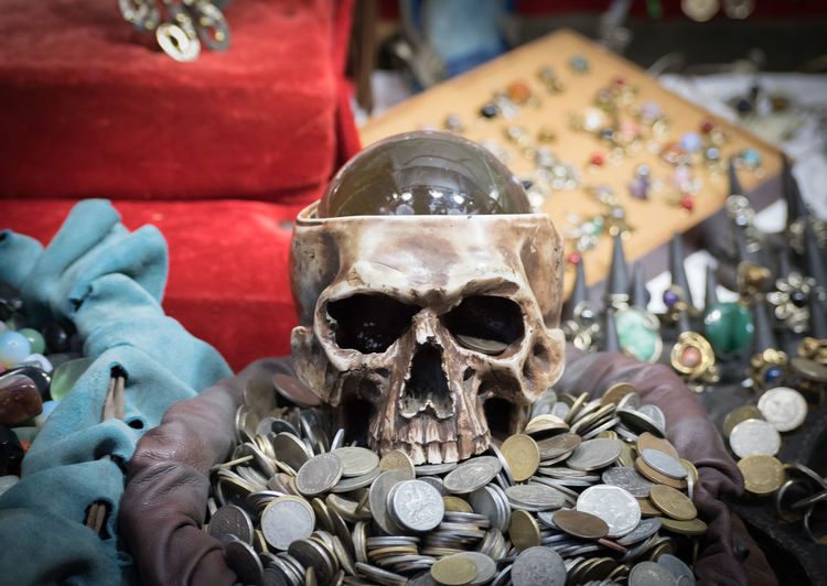 High Angle View Of Human Skull With Coins On Table