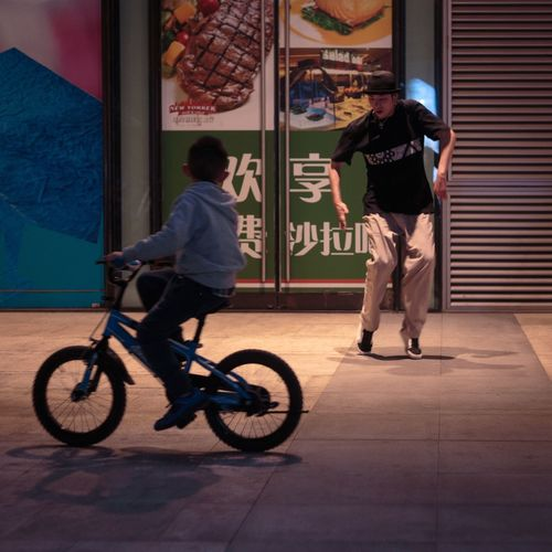 Telling Stories Differently Beijing Kid Dancer Dance Man Nightphotography Night Showing Imperfection Storytelling Story Streetphotography City Street Street Photography Street Up Close Street Photography Ride Dedication Cities At Night CyclingUnites The City Light