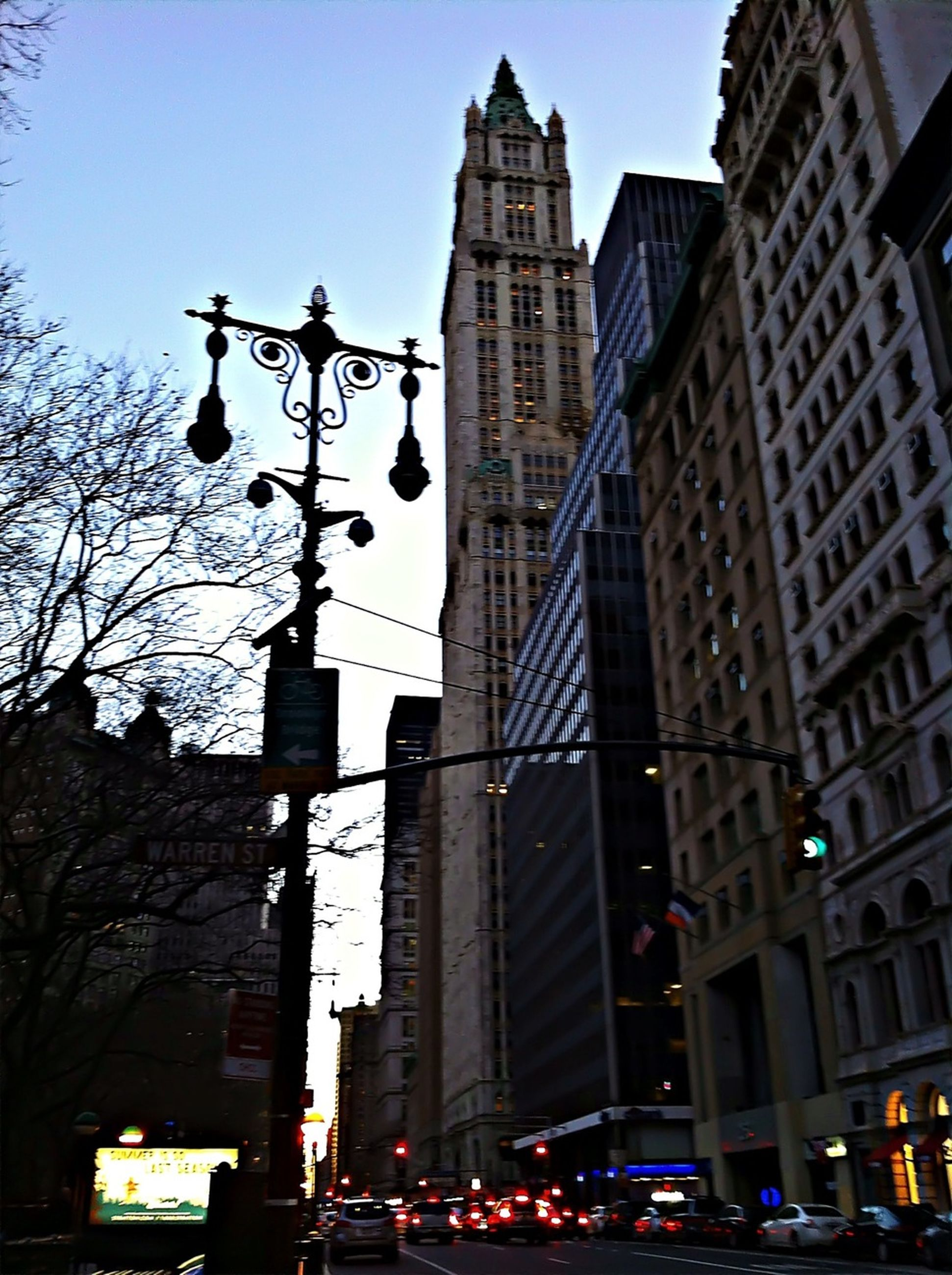 building exterior, architecture, built structure, city, low angle view, car, street, skyscraper, city life, land vehicle, tall - high, street light, transportation, office building, tower, building, city street, road signal, clear sky, mode of transport