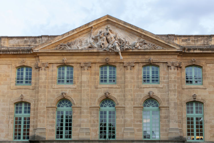 High section of the public library at Aix-en-Provence Arch Architectural Column Architecture Building Building Exterior Built Structure City City Life Cloud - Sky Day Façade History Library Low Angle View No People Outdoors Pediment Sky The Past Weathered Window