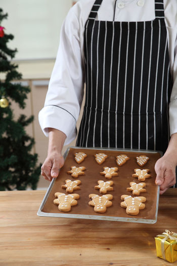 Midsection Of Chef Preparing Gingerbread Cookies On Table