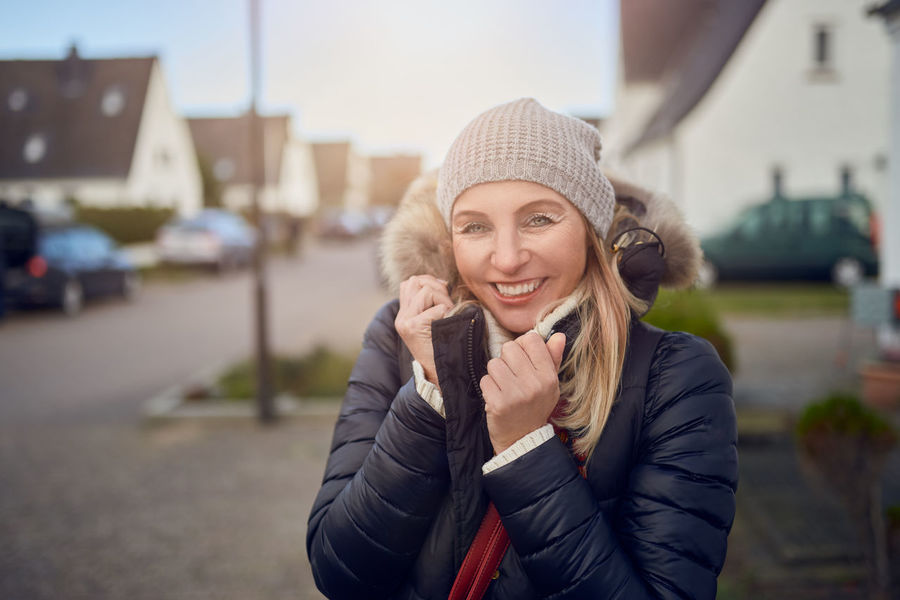 Smiling happy woman outdoors on a cold winter day Happy Snuggling Stylish Best Ager Coat Cold Cold Temperature Communication Fashionable Focus On Foreground Front View Happiness Jacket Knit Hat Leisure Activity Lifestyles Middle-aged One Person Outdoors Real People Smiling Standing Walking Warm Clothing Winter