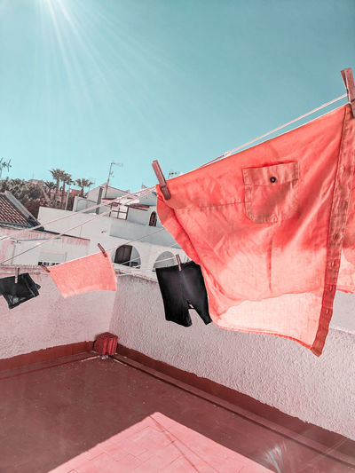 colorful laundry on the roof Coral Colored Orange Color Rooftops SPAIN Mediterranean  Sunlight And Shadow Subtropical Shirt Towel Red City Sky Clothesline Drying Fabric Hanging Laundry Clothes Cloth Clothespin