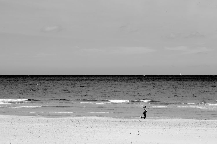Running Solo Black & White Running Beach Blackandwhite Horizon Over Water Jogging Leisure Activity Nature One Person Outdoors Real People Sand Scenics Sea Shore Sport Water Wave