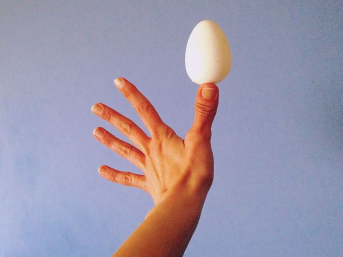 Cropped image of hand balancing egg on thumb against blue background