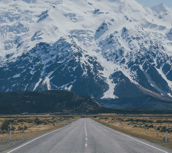 View Of Road Against Snowcapped Mountains