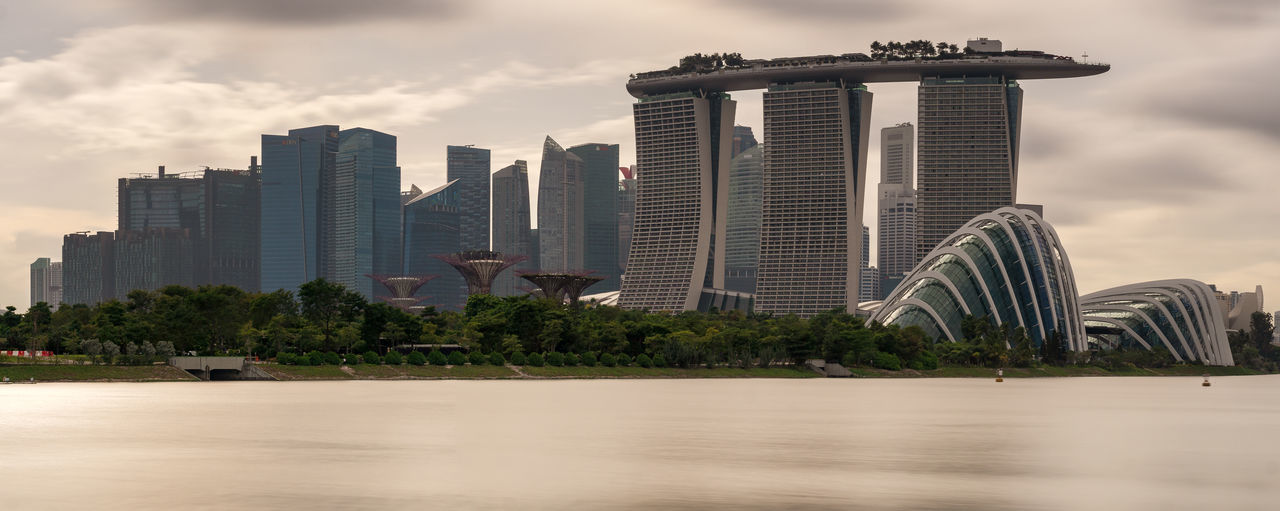 Long exposure shot of the Singapore skyline at daytime Singapore Long Exposure Water City Cityscape Skyline Building Offices Marina Bay Sands Daytime No People Marina Bay Gardens Clouds Panorama Panoramic Waterfront Calm Luxury Hotel Office Building Hotel Tower Tall - High