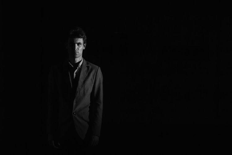 Portrait Of Businessman Standing In Dark Against Black Background