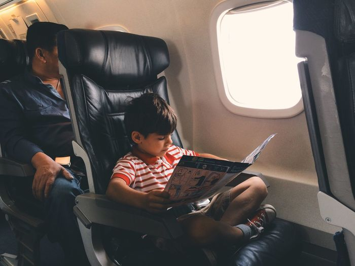 Boy Reading Safety Instructions While Traveling In Airplane