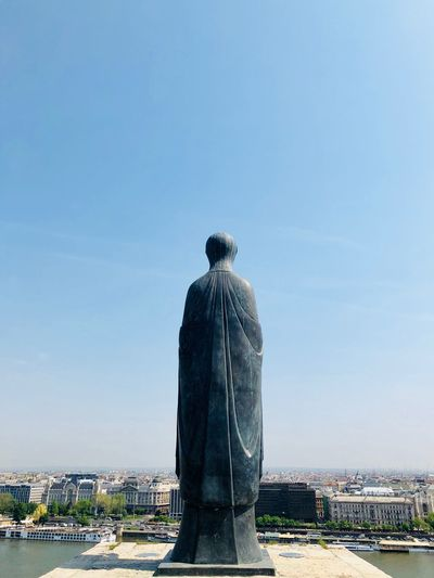 Statue against cityscape and blue sky