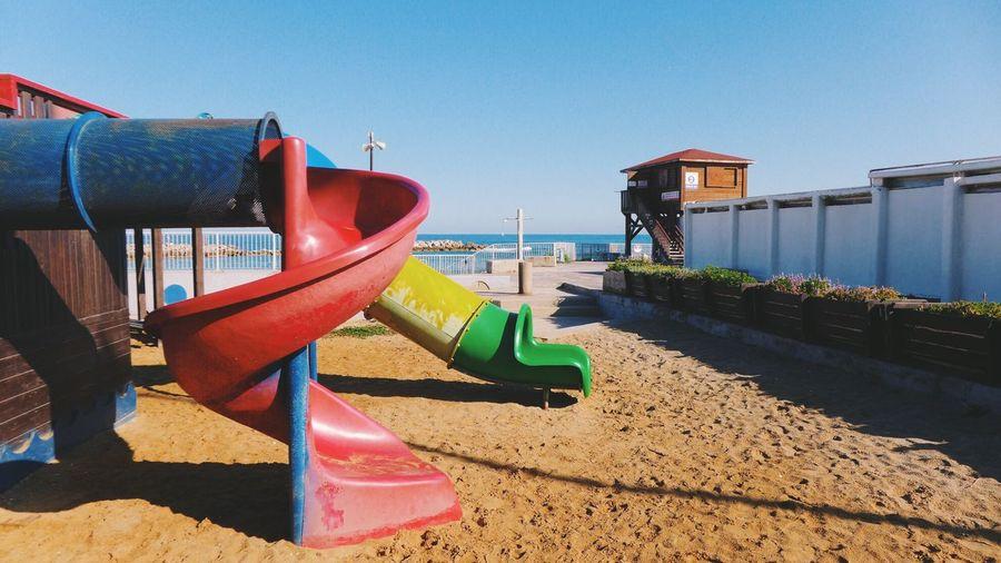 Slides on sand at beach against sky
