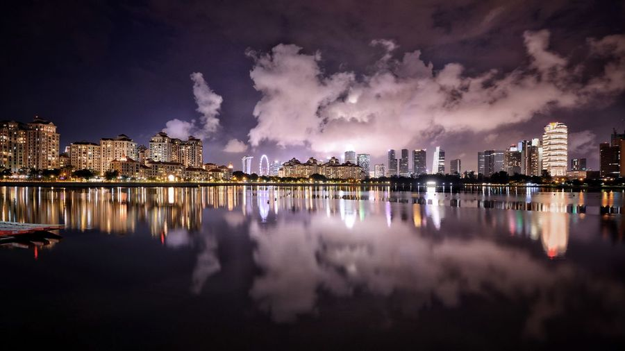 Panoramic view of lake by illuminated buildings against sky at night