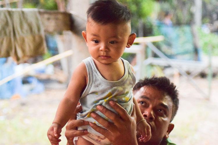 Man Carrying Baby Boy