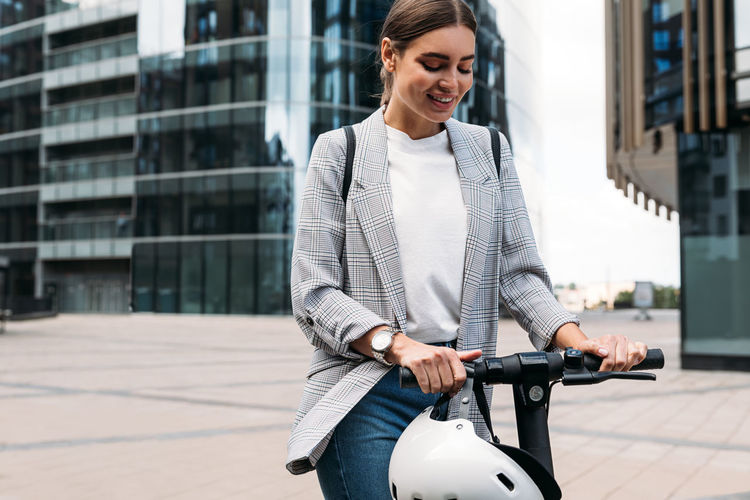 Smiling young woman with bicycle in city