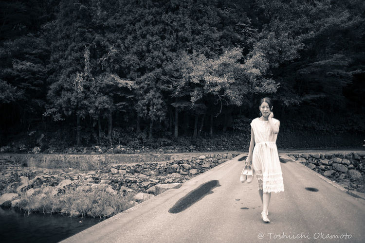 Digital composite image of woman walking along plants