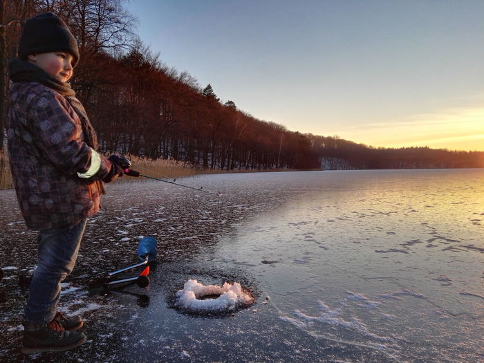Side view of cute boy fishing in frozen lake during sunset