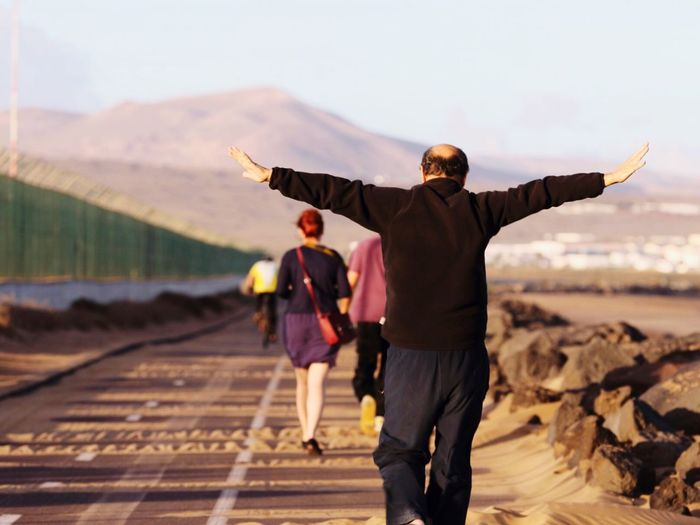Rear View Man Walking With Arms Outstretched On Road