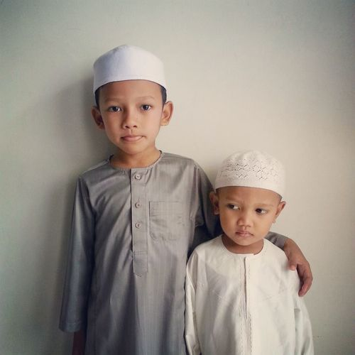 Boys In Traditional Clothing Standing Against Wall