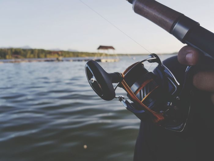 Close-up of hand holding fishing rod against sea