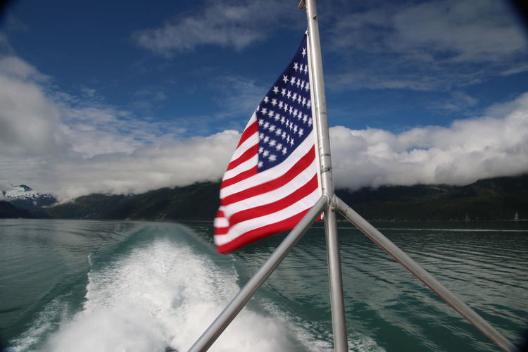 American Flag On Boat Against Cloudy Sky