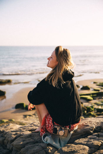 Woman sitting on rock looking at sea shore against sky